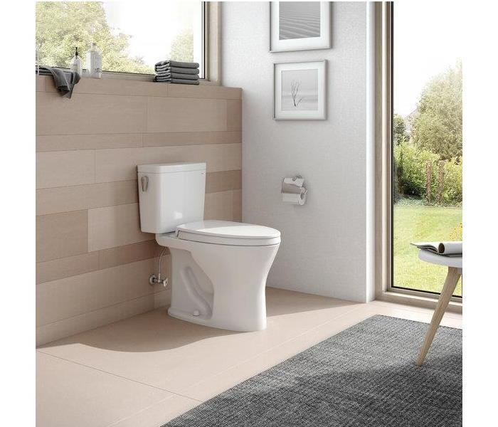 a clean bathroom with a grey rug and a white toilet